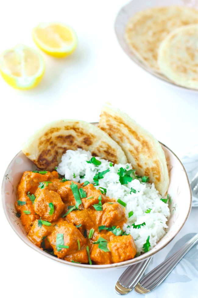 bowl of rice, roti paratha and orange paneer butter curry garnished with coriander. spoon and fork on napkin next to bowl.