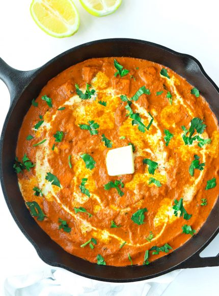 orange paneer curry garnished with cream, unsalted butter and coriander in cast iron skillet