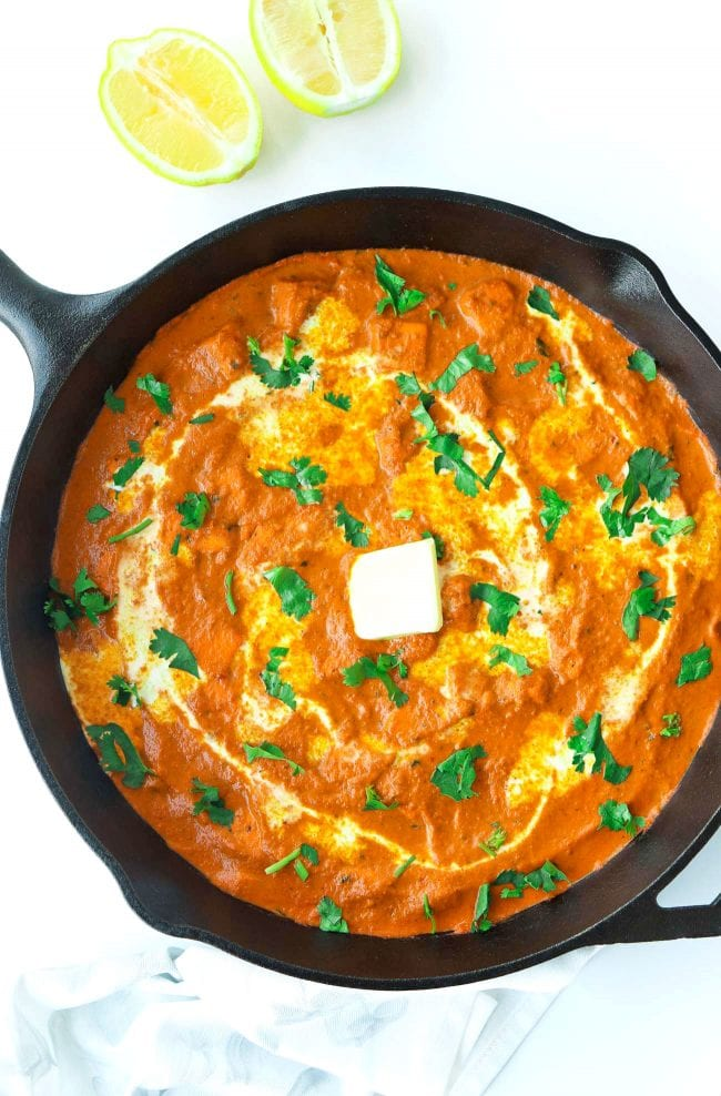 Orange paneer tomato-cream curry garnished with cream, unsalted butter and coriander in cast iron skillet