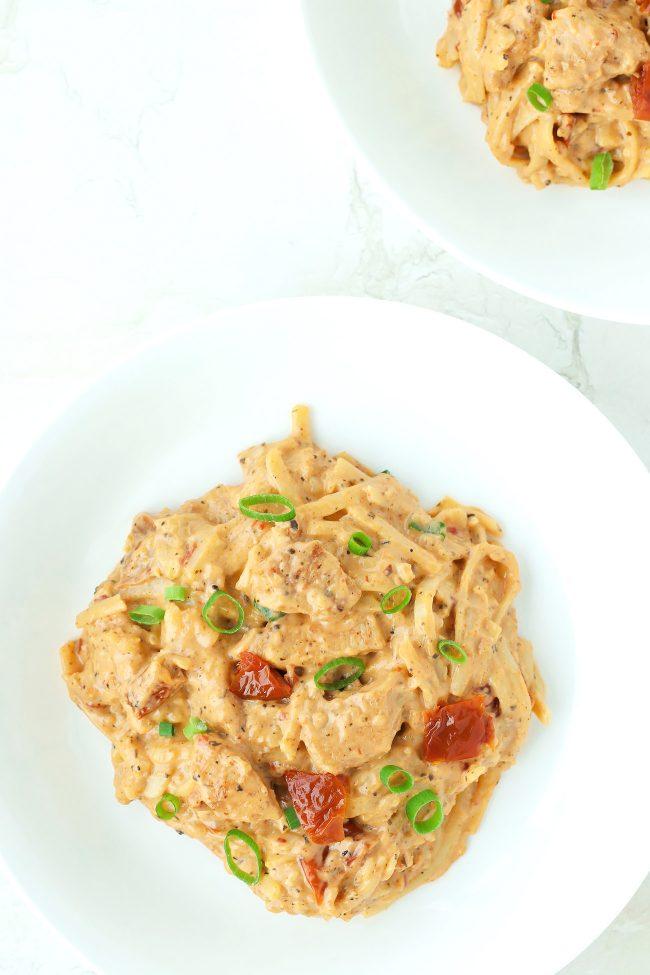 Sundried Tomato Pesto Pasta with Cajun Chicken on two white round plates