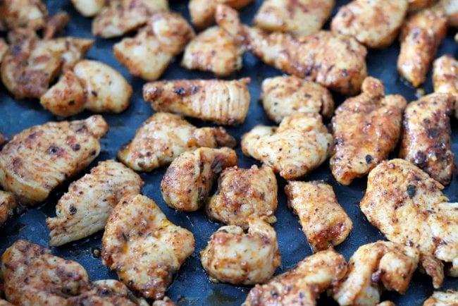 Cajun chicken pieces cooking in pan