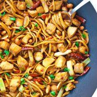 Spicy Asian Chicken Noodles twirled around a fork in a wok