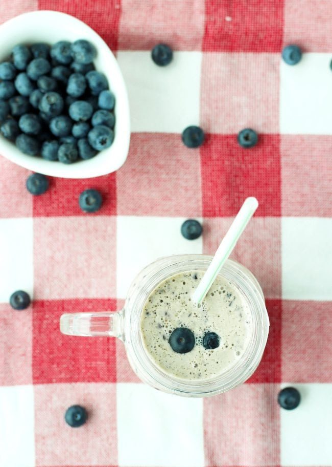 Blueberry banana smoothie in a mason jar mug with a straw and a small white dish with blueberries behind the mug. Blueberry scatter around mug.