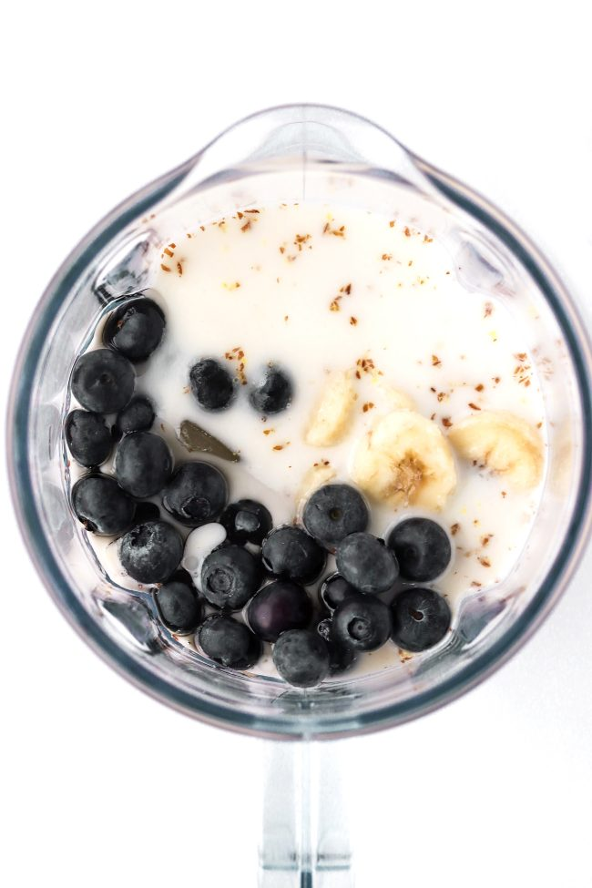 Fresh blueberries, banana slices, milk, and ground flaxseed in a blender jug.