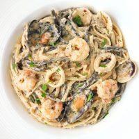 Cream Sauce Seafood Pasta with parsley garnish in deep round white pasta plate