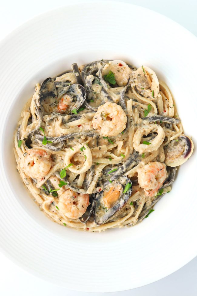 Creamy pasta with seafood topped with parsley garnish in a deep round white pasta plate