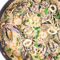 Cream Sauce Seafood Pasta with parsley garnish in a large deep sauté pan