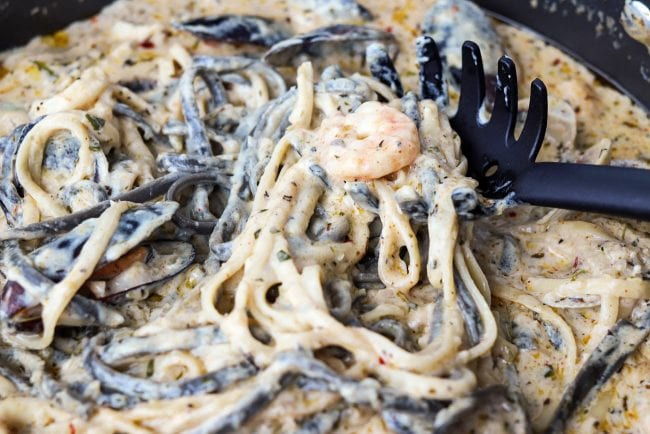 Spaghetti spoon in pan with linguini and creamy sauce with shrimp