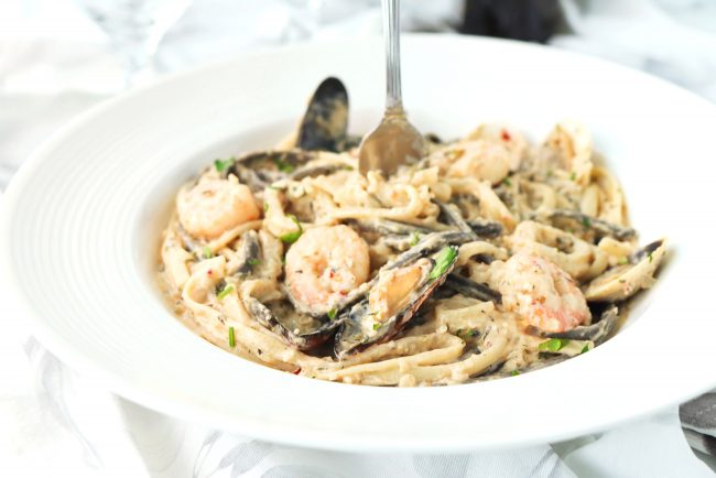 White wine creamy seafood pasta in round white plate. Fork sticking out from center of plate with creamy linguini twirled around it.