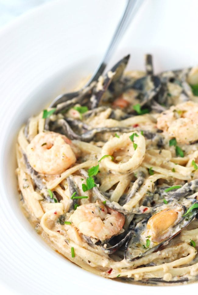 View of half plate filled with cream sauce seafood pasta with a fork
