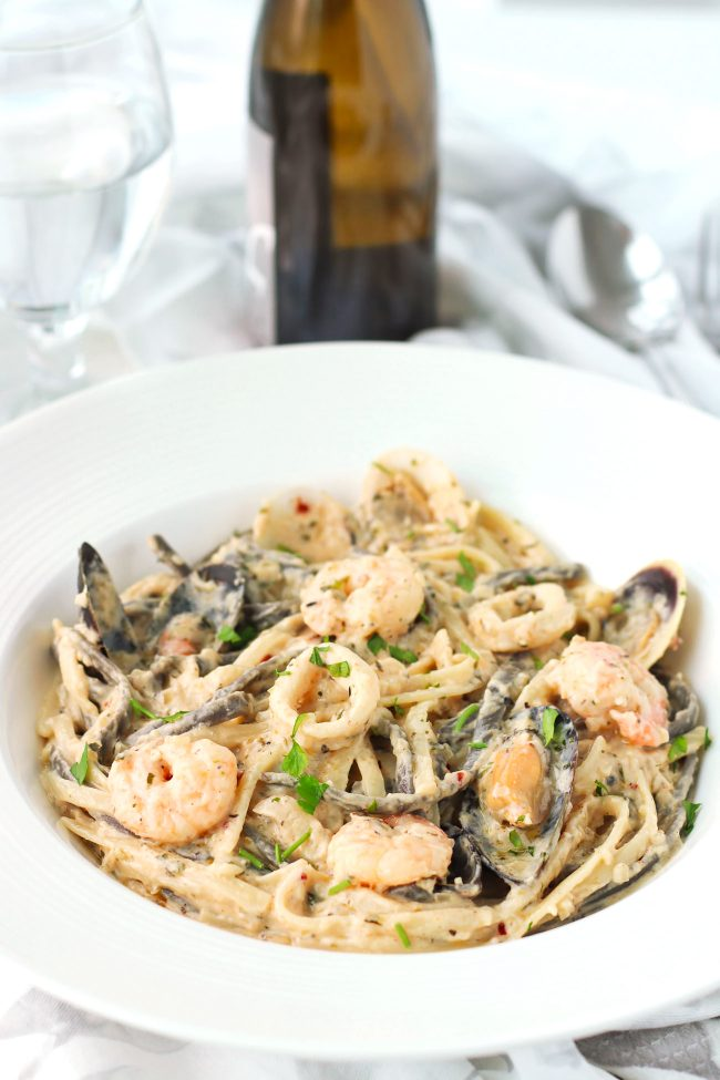 Creamy seafood pasta in a deep round white pasta plate with freshly chopped parsley garnish. White wine bottle and glass of water behind plate.