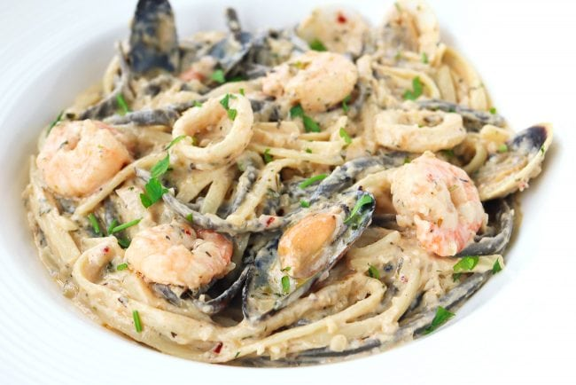 White wine cream sauce pasta with seafood topped with parsley garnish in deep round white pasta plate