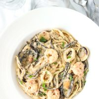 Cream sauce seafood pasta in deep round white pasta plate with freshly chopped parsley garnish. White wine bottle, glass of water, and spoon behind plate.