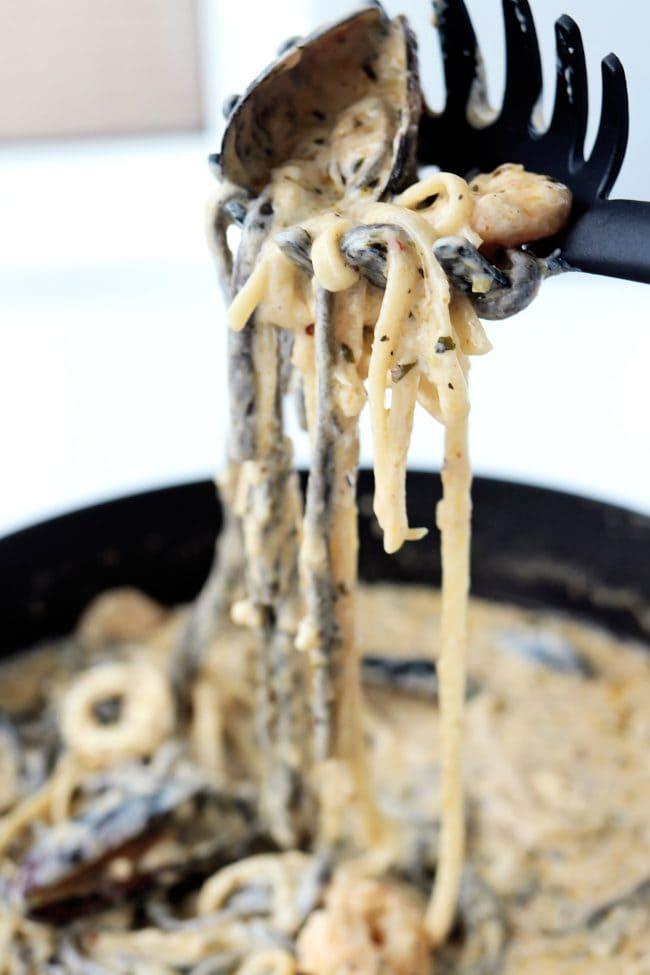 Spaghetti spoon holding up linguini with a piece of shrimp and mussell above a deep large sauté pan filled with the creamy pasta.