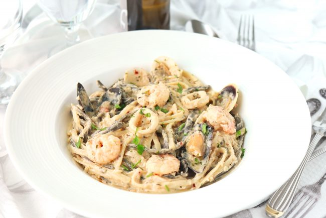 Cream sauce seafood pasta in deep round white pasta plate with freshly chopped parsley garnish. White wine bottle and glass of water behind plate. Forks and spoons on side of plate.