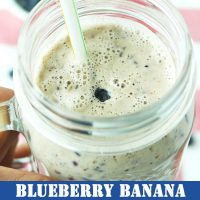 Hand holding up a mason jar mug with Blueberry Banana Smoothie and a straw.