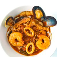 Squid, prawns, mussels, pork, and mushrooms, in a spicy red soup with noodles in a white bowl.