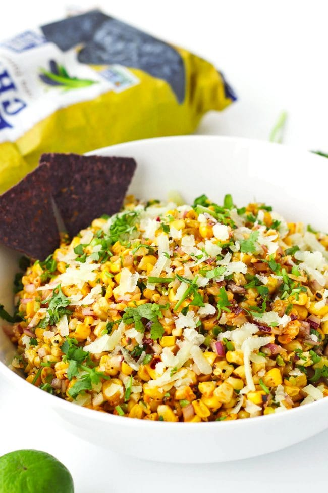 Corn salad in a serving bowl with two blue corn tortilla chips. A lime and bag of tortilla chips surround the bowl.