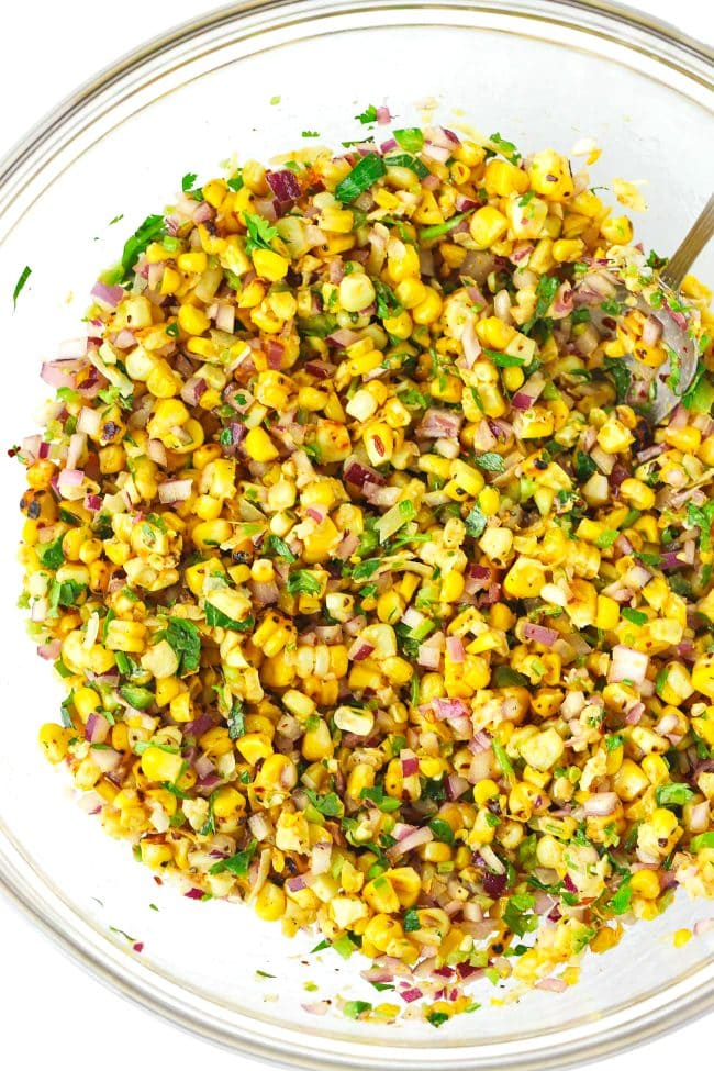 Corn, seasonings, spices, chopped red onion, chopped parsley, chopped coriander, chopped jalapeño, and grated cheese tossed together in a large mixing bowl with a silver spoon.