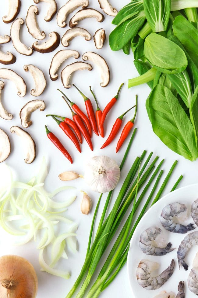 Sliced yellow onion, spring onion, garlic head and cloves, jumbo prawns, red chilies, sliced black mushrooms, and chopped bok choy.