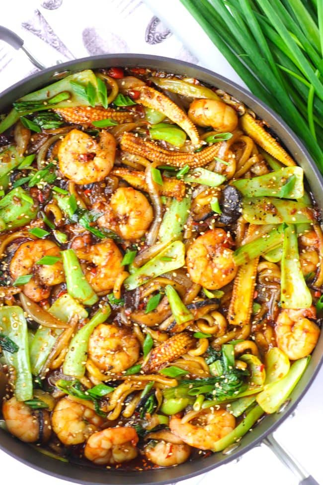 Sichuan Sauce Noodle Stir fry with prawns in a wok with a spring onion bunch behind the wok