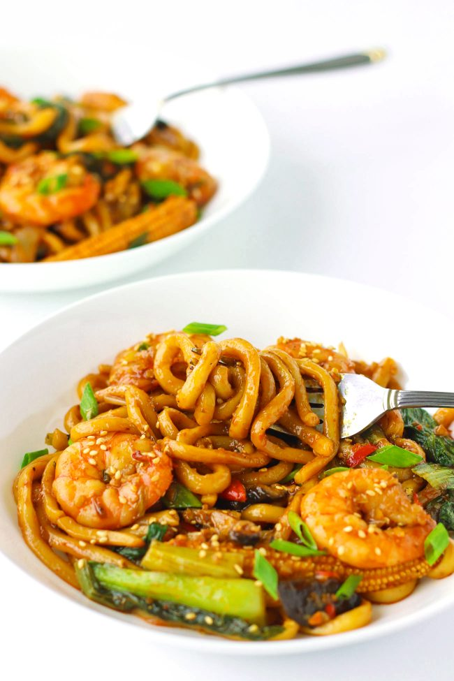 Stir-fry Sichuan Sauce Noodles with Jumbo prawns, baby corn, mushrooms, bok choy, and spring onion garnish on two white plates. Noodles twirled around fork.