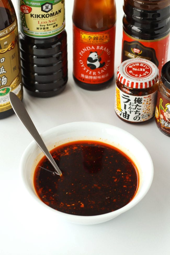 Asian sauce bottles and a bowl with the sauces combined in it with a spoon.