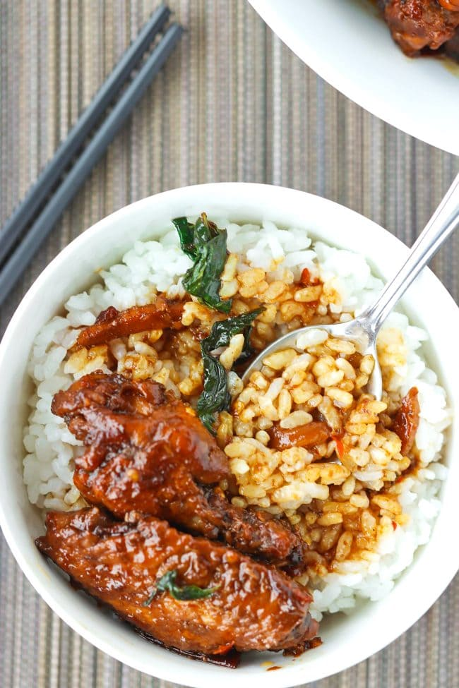 Two pieces of brown sauce glazed chicken wings with sauce on top of steamed white rice in a bowl with a spoon.