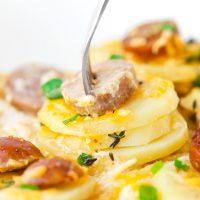 Sliced sausage and cheesy potato rounds garnished with spring onion and fresh thyme in a plate with a fork sticking out of a sausage slice and three potato rounds.