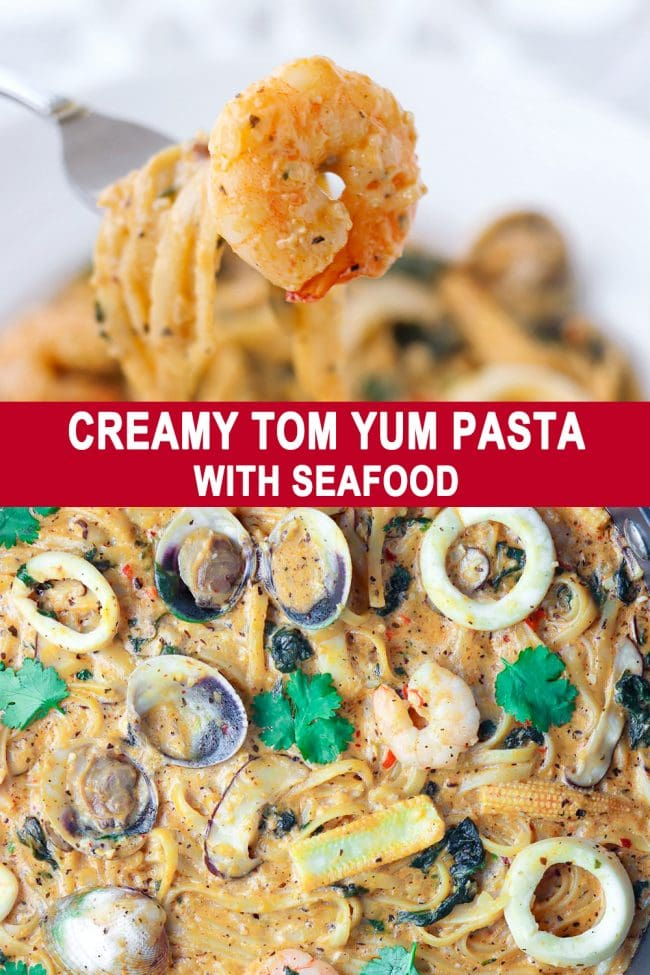 Fork with piece of shrimp at the tip and creamy tom yum pasta with seafood in large pan.