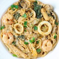 Creamy Tom Yum Pasta with seafood in a white round plate
