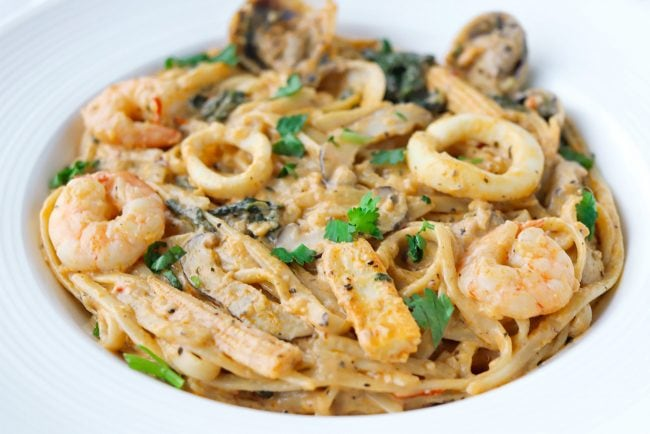 Creamy orange-white pasta with seafood, baby corn, mushrooms, and chopped coriander in a white plate.