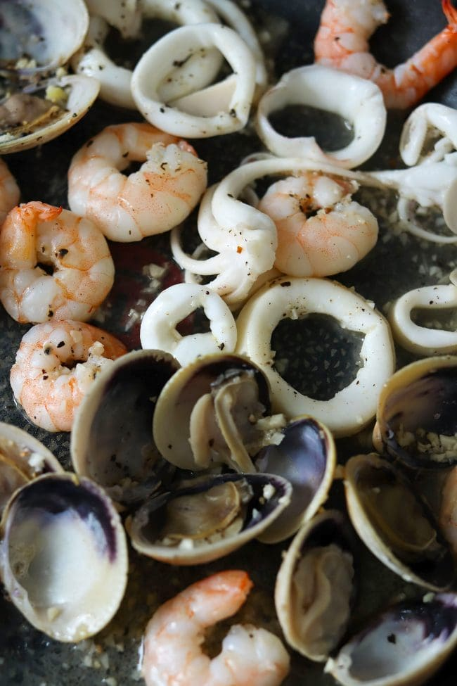 Shrimps, clams, and squid cooking in a pan with oil, garlic, salt, pepper, and lime juice