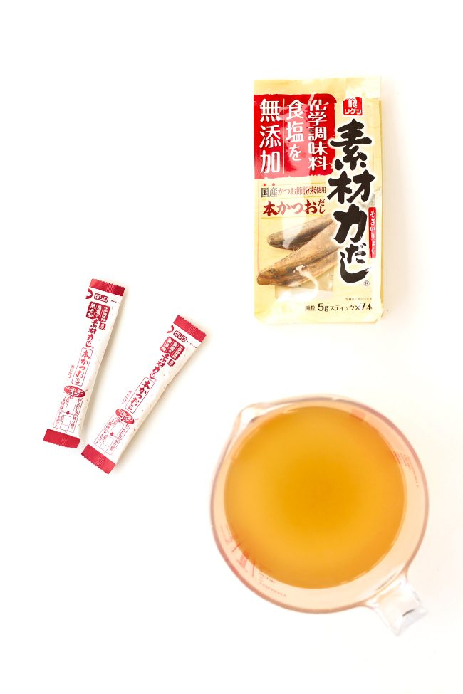 Dashi (Japanese fish stock) in measuring cup, dashi powder sachets, and dashi powder package.