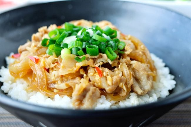 Japanese Pork over white rice in a black bowl and garnished with chopped spring onion.