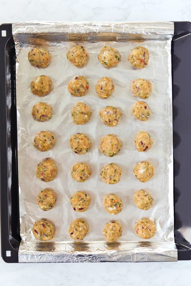 Uncooked ground chicken balls in rows on a foil lined baking tray.