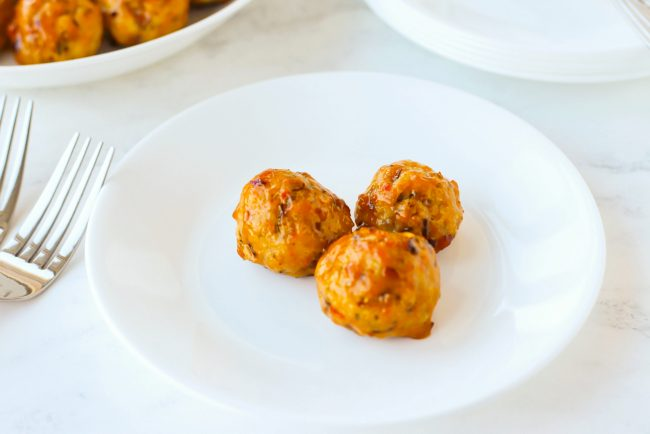 Three chicken meatballs on a small white round plate and two forks on the side of the plate.