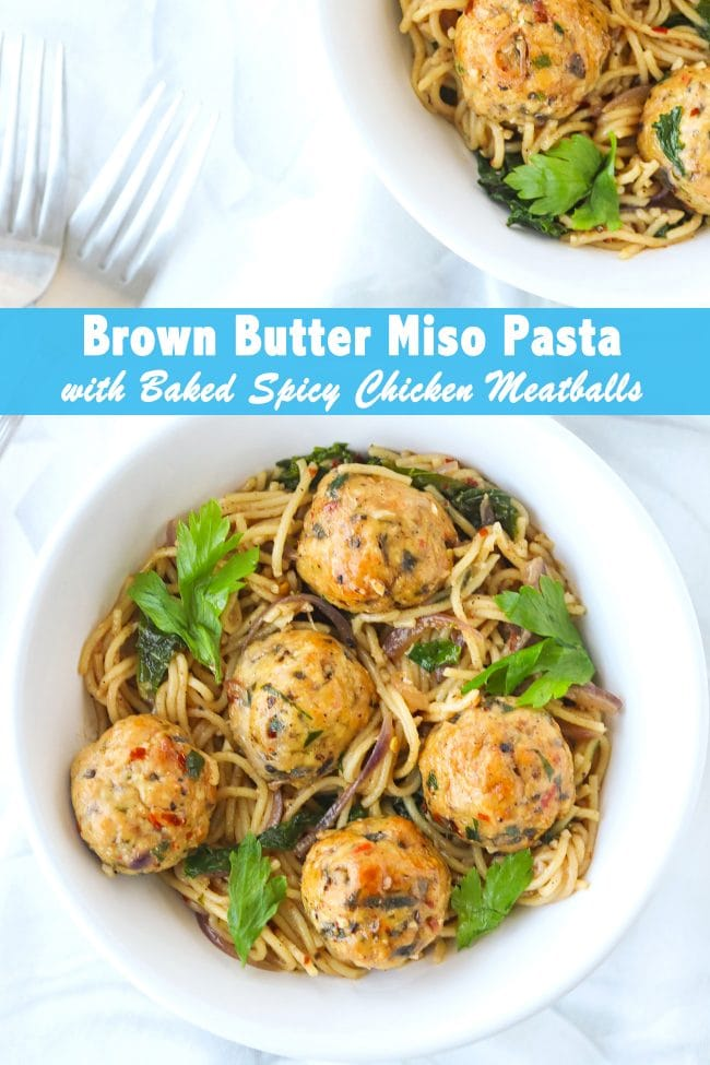 Two diagonally placed white bowls with Brown Butter Miso Pasta with baked chicken meatballs. Two silver forks are on the side of the bowls.