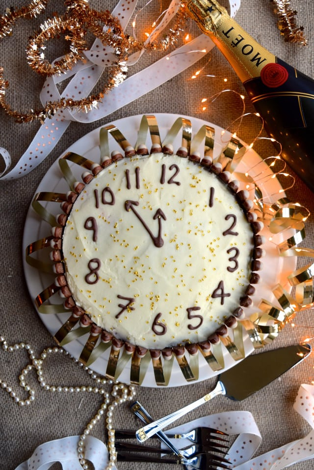 Chocolate Cake with clock numbers and hands and surrounded by chocolate fingers. Cake surrounded with Christmasy festive lights, ribbons, forks, cake cutter, and bottle of Moët.