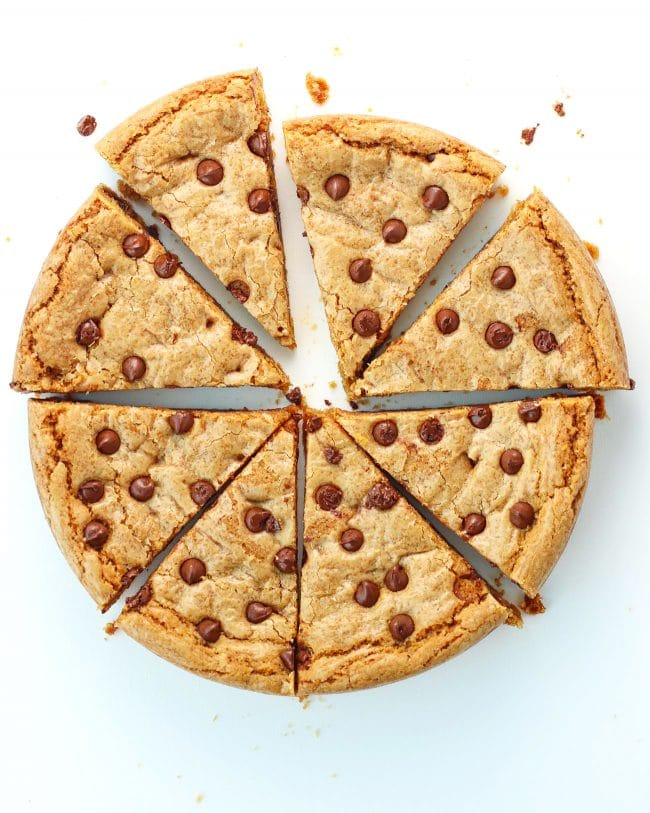 Sliced Chocolate Chip & Butterscotch Chip Cookie Cake with cookie crumbs scattered around.