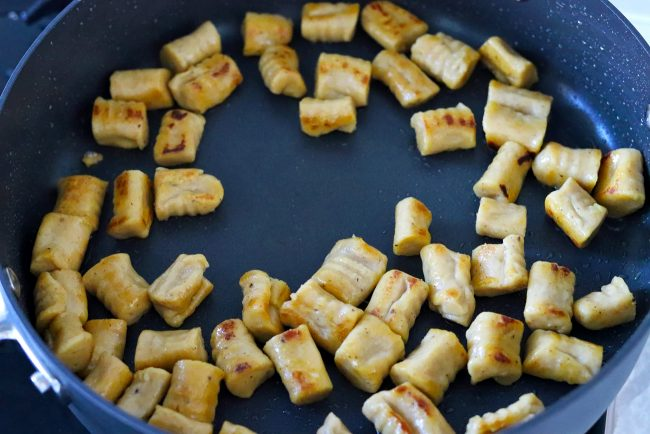 Sweet potato gnocchi pieces crisping up in butter in a large black sauté pan.