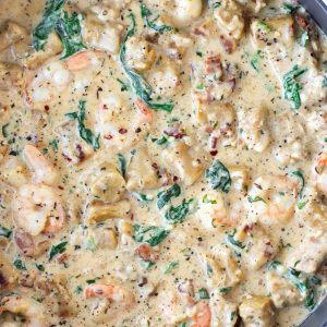 A deep large black sauté pan with sweet potato gnocchi, crispy bacon, shrimp, baby kale, and parsley in a spicy white wine garlic cream sauce.