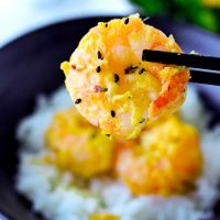 Black chopsticks holding up a mango mayonnaise coated prawn above a bowl with rice and mango mayonnaise prawns.