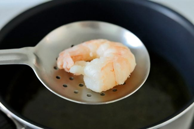 Metal slotted spoon with a deep-fried crispy prawn above a pot with oil.