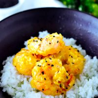 Mango mayonnaise prawns topped with toasted black sesame seeds on top of white rice in a black bowl.