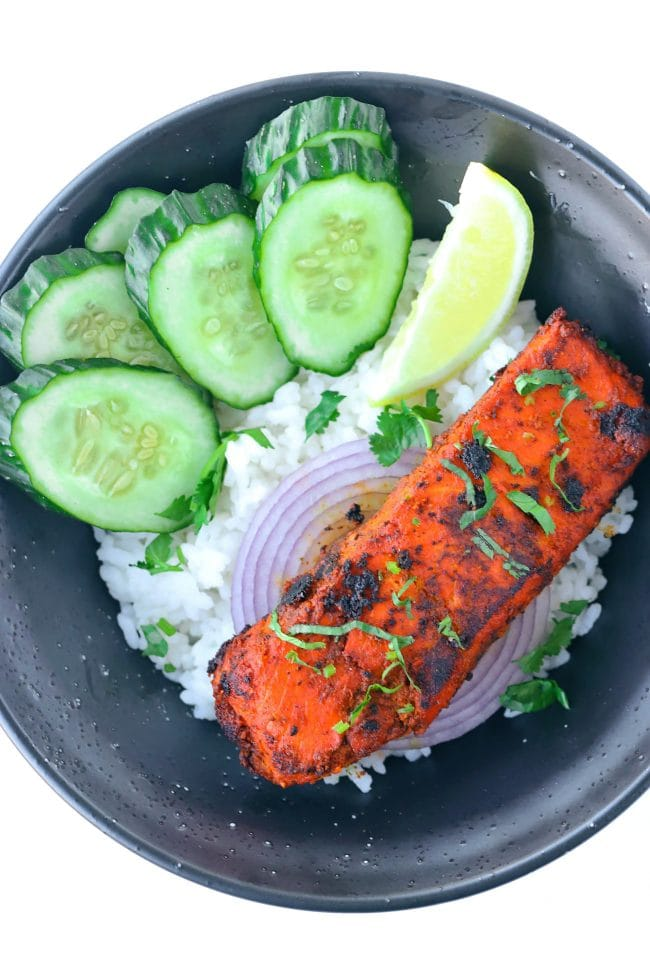 Indian spicy salmon fillet garnished with chopped coriander on top of red onion rings in a bowl with rice, cucumber slices, and a lemon wedge.