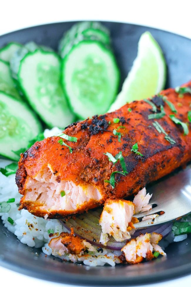 A fork with a bite of spicy Indian salmon and fillet garnished with coriander in a bowl of rice with cucumber slices, red onion, and a lemon wedge.