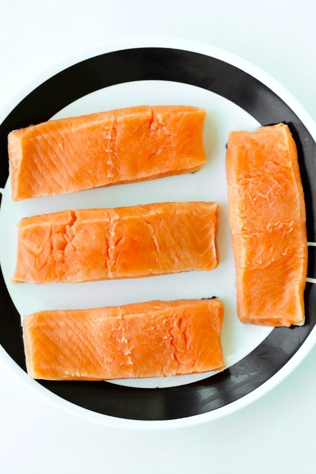 Four raw cleaned salmon fillets on a round plate.