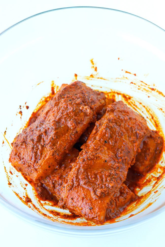 Salmon fillets coated with orange-red spiced paste-like marinade in a large mixing bowl.