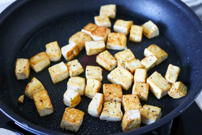Browned salt and pepper seasoned tofu cubes in a black nonstick skillet with a bit of oil.